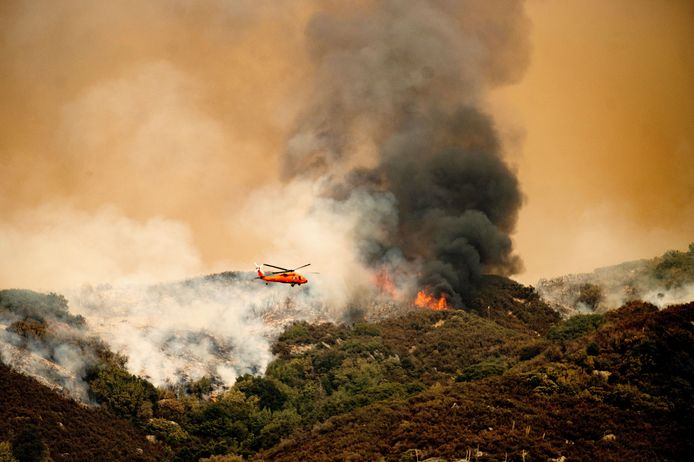 A helicopter drops water over Sequoia National Park in an attempt to put out fires.